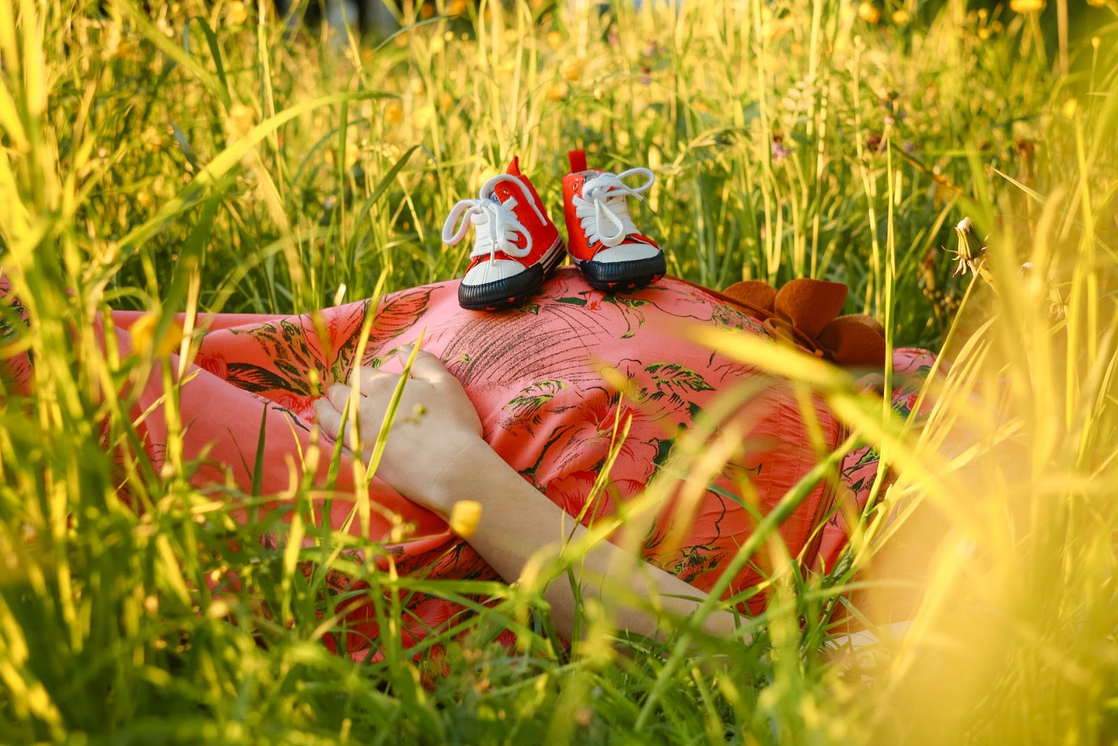 Femme enceinte allongée avec chaussures de bébé sur le ventre